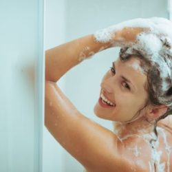 Smiling young woman washing head with shampoo